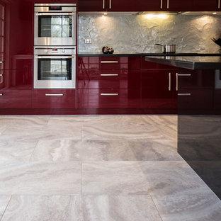 Modern inredning av ett mellanstort kök, med en dubbel diskho, röda skåp, bänkskiva i kvarts, grått stänkskydd, glaspanel som stänkskydd, rostfria vitvaror, klinkergolv i porslin och en köksö