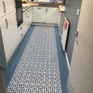 マンチェスターの小さいコンテンポラリースタイルのおしゃれなキッチン (ドロップインシンク、フラットパネル扉のキャビネット、白いキャビネット、木材カウンター、青いキッチンパネル、パネルと同色の調理設備、クッションフロア) の写真