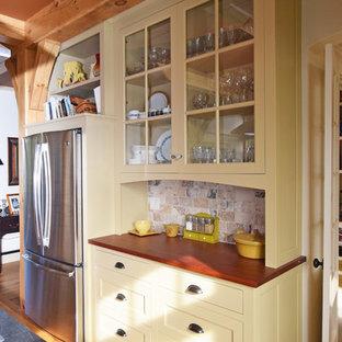 バーリントンの大きいカントリー風おしゃれなキッチン (シングルシンク、インセット扉のキャビネット、黄色いキャビネット、木材カウンター、ベージュキッチンパネル、石タイルのキッチンパネル、シルバーの調理設備、淡色無垢フローリング) の写真