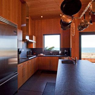 Ejemplo de cocina en L, minimalista, grande, abierta, con fregadero bajoencimera, armarios con paneles lisos, puertas de armario de madera oscura, encimera de granito, salpicadero azul, salpicadero de azulejos de cerámica, electrodomésticos de acero inoxidable, suelo de cemento y una isla