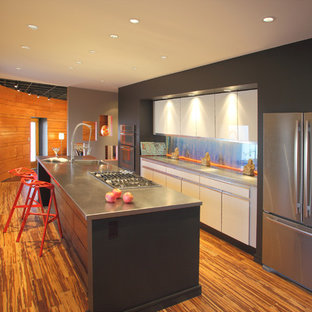 Kitchen - contemporary galley kitchen idea in Other with stainless steel appliances, an integrated sink, flat-panel cabinets, white cabinets and stainless steel countertops