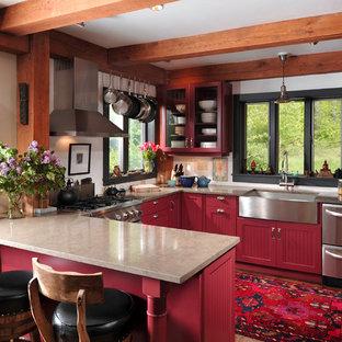 Cette photo montre une cuisine montagne en U de taille moyenne avec un électroménager en acier inoxydable, un évier de ferme, des portes de placard rouges, un sol marron, un placard à porte persienne, un plan de travail en granite et un sol en bois foncé.