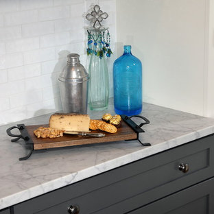 Mid-sized transitional eat-in kitchen ideas - Mid-sized transitional u-shaped dark wood floor and brown floor eat-in kitchen photo in Milwaukee with a farmhouse sink, shaker cabinets, gray cabinets, white backsplash, subway tile backsplash, stainless steel appliances, a peninsula, marble countertops and gray countertops