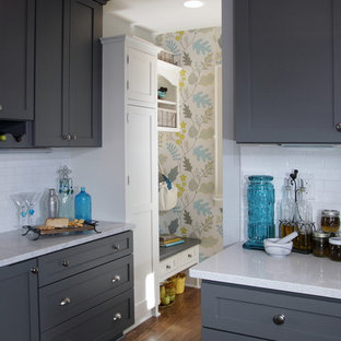 Mid-sized transitional eat-in kitchen designs - Mid-sized transitional u-shaped dark wood floor and brown floor eat-in kitchen photo in Milwaukee with a farmhouse sink, shaker cabinets, gray cabinets, white backsplash, subway tile backsplash, stainless steel appliances, a peninsula, quartzite countertops and gray countertops