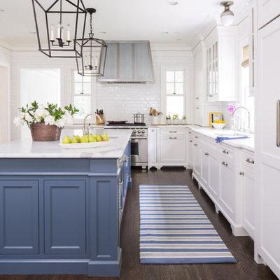 Kitchen - traditional dark wood floor kitchen idea in New York with an undermount sink, shaker cabinets, white cabinets, white backsplash, subway tile backsplash, stainless steel appliances and an island