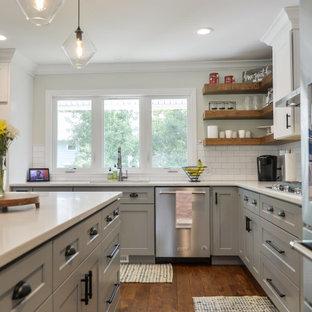 Große Klassische Küche in L-Form mit Einbauwaschbecken, Schrankfronten im Shaker-Stil, grauen Schränken, Küchenrückwand in Weiß, Rückwand aus Metrofliesen, Küchengeräten aus Edelstahl, braunem Holzboden, Kücheninsel, braunem Boden und weißer Arbeitsplatte in Philadelphia