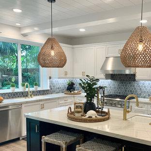オレンジカウンティの中サイズのビーチスタイルのおしゃれなキッチン (アンダーカウンターシンク、シェーカースタイル扉のキャビネット、白いキャビネット、珪岩カウンター、グレーのキッチンパネル、セメントタイルのキッチンパネル、シルバーの調理設備の、クッションフロア、ベージュの床、グレーのキッチンカウンター) の写真
