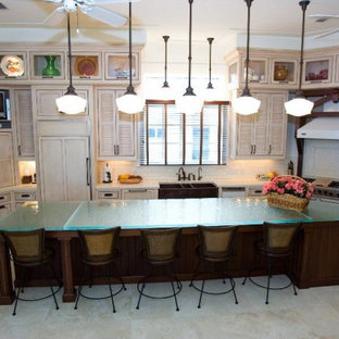 Photo of a large u-shaped kitchen in Austin with a triple-bowl sink, louvered cabinets, distressed cabinets, glass benchtops, beige splashback, stone tile splashback, panelled appliances, porcelain floors, with island, beige floor and blue benchtop.