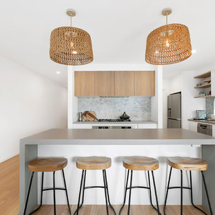 Contemporary u-shaped open plan kitchen in Melbourne with an undermount sink, flat-panel cabinets, white cabinets, quartz benchtops, grey splashback, stone tile splashback, stainless steel appliances, medium hardwood floors, with island and grey benchtop.