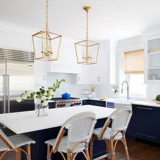 フィラデルフィアの中サイズのビーチスタイルのおしゃれなキッチン (エプロンフロントシンク、白いキッチンパネル、サブウェイタイルのキッチンパネル、シルバーの調理設備の、濃色無垢フローリング、茶色い床、白いキッチンカウンター、落し込みパネル扉のキャビネット、青いキャビネット) の写真