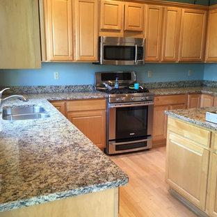 ミネアポリスの中サイズのシャビーシック調のおしゃれなキッチン (アンダーカウンターシンク、フラットパネル扉のキャビネット、淡色木目調キャビネット、御影石カウンター、黒いキッチンパネル、石スラブのキッチンパネル、シルバーの調理設備の) の写真