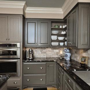 Esempio di una cucina a L chic di medie dimensioni con ante con bugna sagomata, ante grigie, paraspruzzi grigio, elettrodomestici in acciaio inossidabile, top in granito, pavimento in legno verniciato, isola, paraspruzzi in marmo e lavello sottopiano