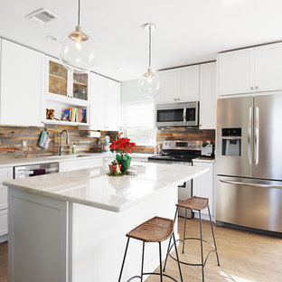 Ejemplo de cocina clásica renovada, pequeña, abierta, con fregadero bajoencimera, armarios estilo shaker, puertas de armario blancas, encimera de mármol, electrodomésticos de acero inoxidable, suelo de madera clara, una isla, salpicadero marrón y salpicadero de pizarra
