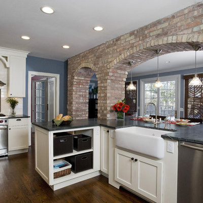 Eat-in kitchen - mid-sized traditional u-shaped medium tone wood floor and brown floor eat-in kitchen idea in Chicago with stainless steel appliances, subway tile backsplash, a farmhouse sink, soapstone countertops, shaker cabinets, white cabinets, white backsplash and black countertops