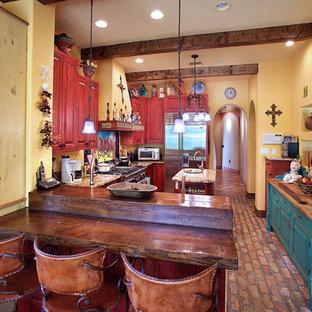 Geschlossene Mediterrane Küche mit roten Schränken, profilierten Schrankfronten, Arbeitsplatte aus Holz, Küchengeräten aus Edelstahl und Backsteinboden in Tampa
