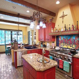 Diseño de cocina de estilo americano con electrodomésticos de acero inoxidable, fregadero encastrado, armarios con paneles con relieve, salpicadero multicolor, suelo de ladrillo y puertas de armario de madera oscura