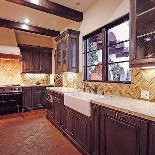 Foto på ett stort medelhavsstil kök, med en rustik diskho, luckor med upphöjd panel, skåp i slitet trä, bänkskiva i kalksten, beige stänkskydd, stänkskydd i stickkakel, integrerade vitvaror, tegelgolv och en köksö