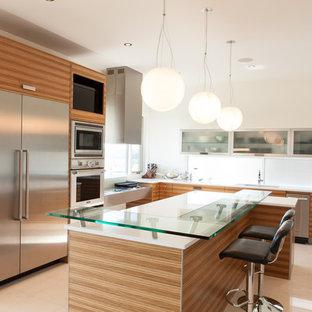 Inspiration för ett funkis l-kök, med rostfria vitvaror, bänkskiva i glas, en undermonterad diskho, släta luckor och skåp i mellenmörkt trä