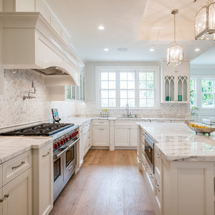 Kitchen - large traditional l-shaped light wood floor kitchen idea in Los Angeles with marble countertops, ceramic backsplash, stainless steel appliances, an island, recessed-panel cabinets, white cabinets and white backsplash