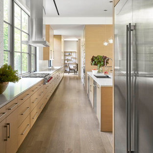 Contemporary kitchen ideas - Trendy galley medium tone wood floor and brown floor kitchen photo in Dallas with an undermount sink, flat-panel cabinets, medium tone wood cabinets, white backsplash, window backsplash, stainless steel appliances, an island and white countertops