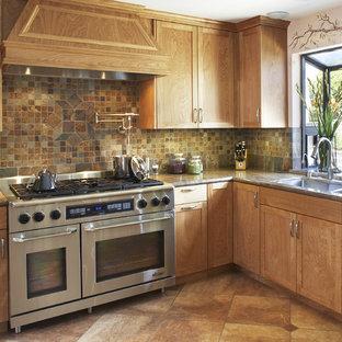 Imagen de cocina mediterránea con fregadero de doble seno, armarios estilo shaker, puertas de armario de madera oscura, salpicadero marrón, electrodomésticos de acero inoxidable y salpicadero de pizarra