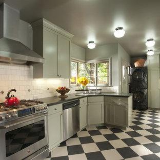 Cette photo montre une cuisine chic fermée avec un électroménager en acier inoxydable, un placard à porte shaker, des portes de placards vertess, une crédence blanche et un sol multicolore.