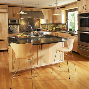 Удачное сочетание для дизайна помещения: угловая кухня в современном стиле с фасадами в стиле шейкер, светлыми деревянными фасадами, техникой из нержавеющей стали, столешницей из гранита и фартуком из сланца - самое интересное для вас