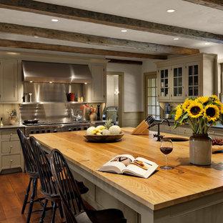 ニューヨークの巨大なカントリー風おしゃれなアイランドキッチン (エプロンフロントシンク、シェーカースタイル扉のキャビネット、グレーのキャビネット、木材カウンター、グレーのキッチンパネル、シルバーの調理設備、無垢フローリング) の写真