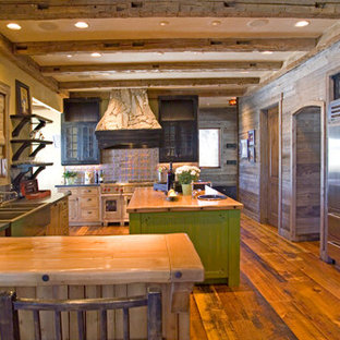 フェニックスの巨大なラスティックスタイルのおしゃれなキッチン (エプロンフロントシンク、フラットパネル扉のキャビネット、中間色木目調キャビネット、木材カウンター、メタリックのキッチンパネル、メタルタイルのキッチンパネル、シルバーの調理設備、無垢フローリング) の写真