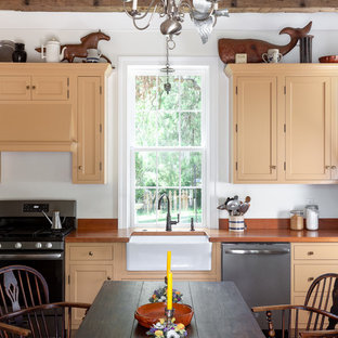 Farmhouse eat-in kitchen ideas - Inspiration for a country brick floor eat-in kitchen remodel in Raleigh with a farmhouse sink, shaker cabinets, orange cabinets, stainless steel appliances and orange countertops