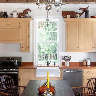 Exemple d'une cuisine américaine nature avec un évier de ferme, un placard à porte shaker, des portes de placard oranges, un électroménager en acier inoxydable, un sol en brique et un plan de travail orange.