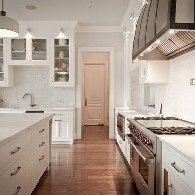 Elegant l-shaped kitchen photo in New York with recessed-panel cabinets, white cabinets, marble countertops, white backsplash, stone slab backsplash and paneled appliances