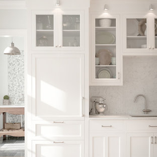 Traditional kitchen ideas - Example of a classic kitchen design in New York with glass-front cabinets, an undermount sink, white cabinets, white backsplash, stone slab backsplash and paneled appliances