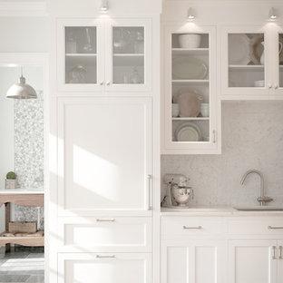 Klassische Küche mit Glasfronten, Unterbauwaschbecken, weißen Schränken, Küchenrückwand in Weiß, Rückwand aus Stein und Elektrogeräten mit Frontblende in New York