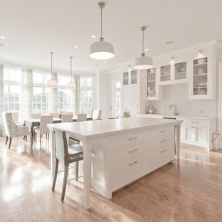 Photo of a traditional eat-in kitchen in New York with glass-front cabinets, marble benchtops, white splashback, stone slab splashback and white cabinets.