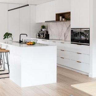 Diseño de cocina de galera, minimalista, de tamaño medio, abierta, con fregadero de doble seno, puertas de armario blancas, encimera de cuarzo compacto, salpicadero blanco, salpicadero de mármol, electrodomésticos blancos, suelo laminado, una isla, suelo marrón y encimeras blancas