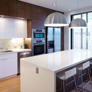 Photo of a modern kitchen in Other with stainless steel appliances, a single-bowl sink, flat-panel cabinets, white cabinets and engineered stone countertops.