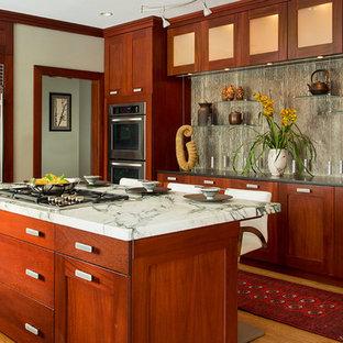 Ejemplo de cocina clásica renovada, grande, con armarios con paneles empotrados, puertas de armario de madera oscura, electrodomésticos de acero inoxidable, una isla y suelo de madera clara