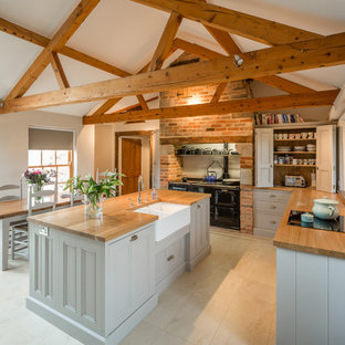 Large country l-shaped kitchen/diner in Other with a belfast sink, recessed-panel cabinets, grey cabinets, wood worktops and an island.