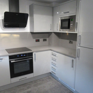 Small modern u-shaped eat-in kitchen in Other with an undermount sink, flat-panel cabinets, grey cabinets, quartzite benchtops, glass sheet splashback, black appliances, vinyl floors, no island, grey floor and grey benchtop.