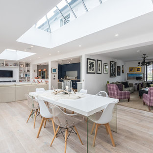 This is an example of a medium sized contemporary galley open plan kitchen in Edinburgh with an integrated sink, shaker cabinets, grey cabinets, composite countertops, grey splashback, glass sheet splashback, white appliances, medium hardwood flooring, a breakfast bar, brown floors and white worktops.
