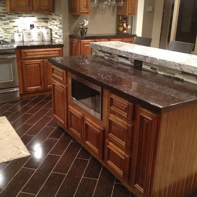 Inspiration for a mid-sized transitional single-wall dark wood floor and brown floor eat-in kitchen remodel in Orange County with raised-panel cabinets, medium tone wood cabinets, granite countertops, multicolored backsplash, matchstick tile backsplash, stainless steel appliances, an island and black countertops