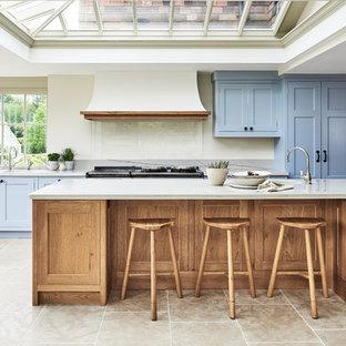 他の地域の広いカントリー風おしゃれなキッチン (落し込みパネル扉のキャビネット、珪岩カウンター、パネルと同色の調理設備、セラミックタイルの床、アンダーカウンターシンク、青いキャビネット、ベージュキッチンパネル) の写真