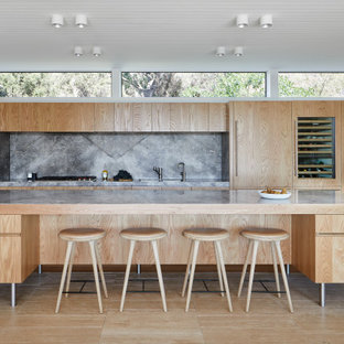 Inspiration for a contemporary open plan kitchen in Melbourne with an undermount sink, flat-panel cabinets, medium wood cabinets, wood benchtops, grey splashback, panelled appliances, medium hardwood floors, with island, brown floor and brown benchtop.
