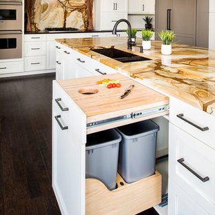 This is an example of a large traditional l-shaped kitchen/diner in New York with a submerged sink, shaker cabinets, white cabinets, granite worktops, multi-coloured splashback, stone slab splashback, integrated appliances, dark hardwood flooring and an island.