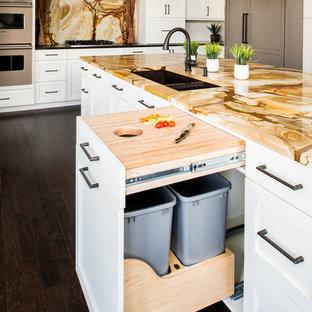 Foto di una grande cucina classica con lavello sottopiano, ante in stile shaker, ante bianche, top in granito, paraspruzzi multicolore, paraspruzzi in lastra di pietra, elettrodomestici da incasso, parquet scuro e isola