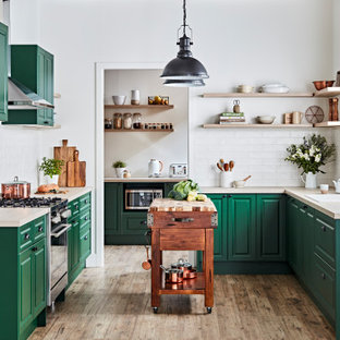 Design ideas for a transitional u-shaped kitchen in Melbourne with a drop-in sink, raised-panel cabinets, green cabinets, wood benchtops, white splashback, subway tile splashback, stainless steel appliances, medium hardwood floors, with island, brown floor and beige benchtop.