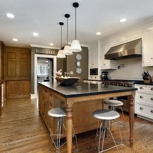 ワシントンD.C.の大きいヴィクトリアン調のおしゃれなキッチン (エプロンフロントシンク、シェーカースタイル扉のキャビネット、白いキャビネット、クオーツストーンカウンター、白いキッチンパネル、セラミックタイルのキッチンパネル、シルバーの調理設備の、淡色無垢フローリング) の写真