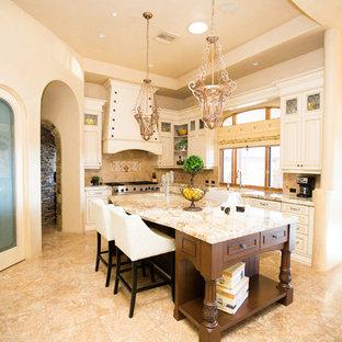 Ejemplo de cocina en U, mediterránea, con fregadero sobremueble, armarios con paneles con relieve, puertas de armario beige, salpicadero beige, una isla y suelo beige