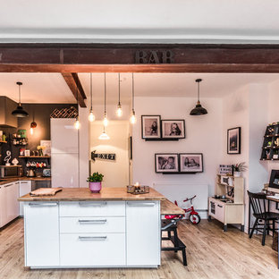 Large contemporary l-shaped kitchen/diner in Cardiff with wood worktops, an island, brown worktops, a single-bowl sink, white cabinets, grey splashback, metal splashback, stainless steel appliances, light hardwood flooring, brown floors and flat-panel cabinets.